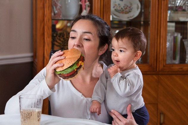 Mother-eating-burger-whilst-holding-her-young-child-1458152.jpg