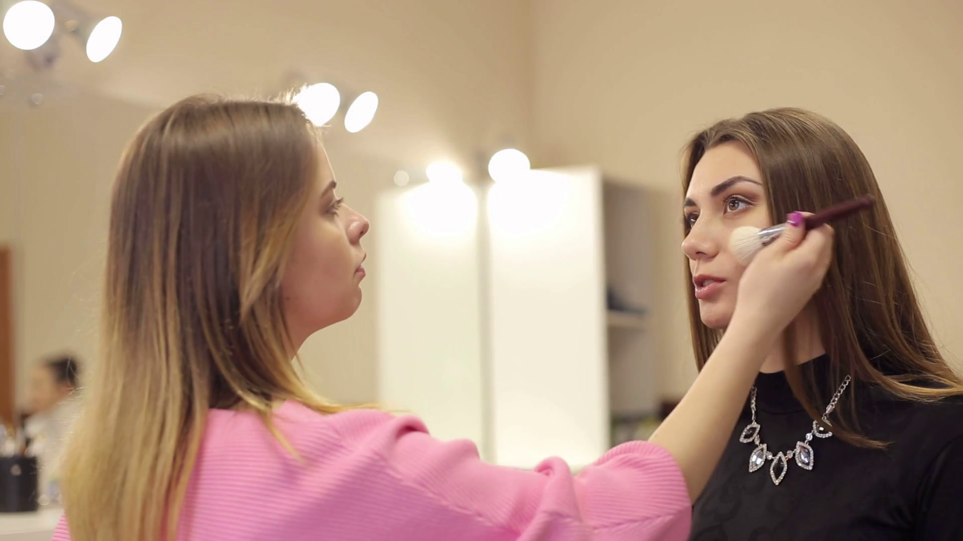videoblocks-young-woman-applying-makeup-to-model-in-beauty-salon-make-up-artist-at-the-work-with-client_rwx2qv4cx_thumbnail-full01.png