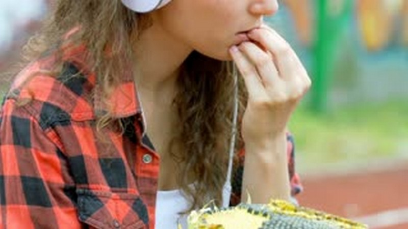 girl-listening-music-on-headphones-and-eating-sunflowers-seeds_sva4wcqn_thumbnail-small01.jpg