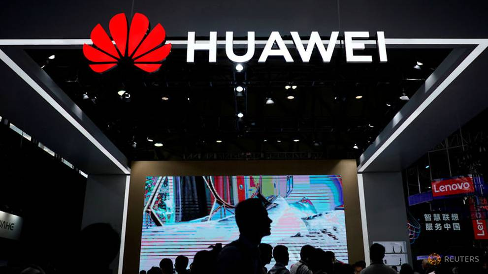file-photo--people-walk-past-a-sign-board-of-huawei-at-ces--consumer-electronics-show--asia-2018-in-shanghai-2.jpg
