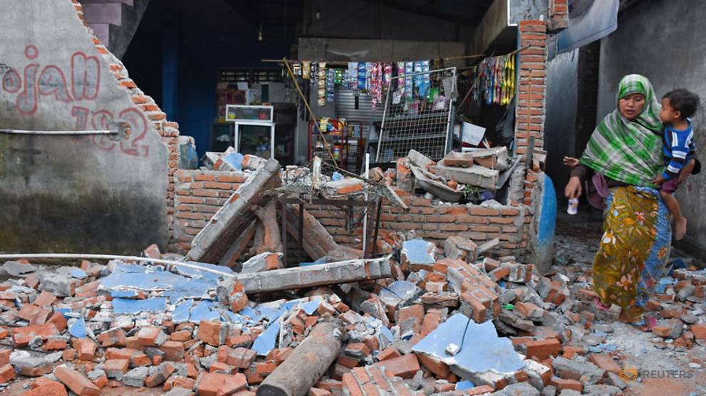 a-woman-walks-past-debris-from-a-collapsed-wall-following-a-strong-earthquake-in-lendang-bajur-hamlet--lombok-2.jpg