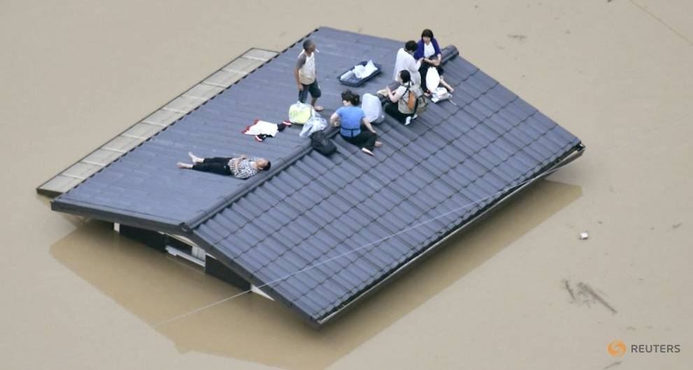an-aerial-view-shows-local-residents-seen-on-the-roof-of-submerged-house-at-a-flooded-area-as-they-wait-for-a-rescue-in-kurashiki-1.jpg