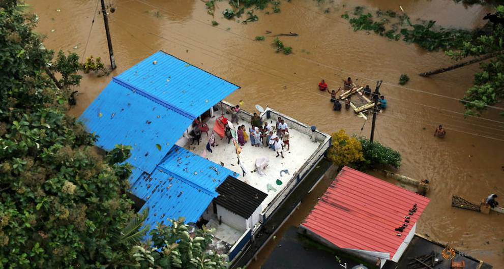 people-wait-for-aid-on-the-roof-of-their-house-at-a-flooded-area-in-the-southern-state-of-kerala-2.jpg